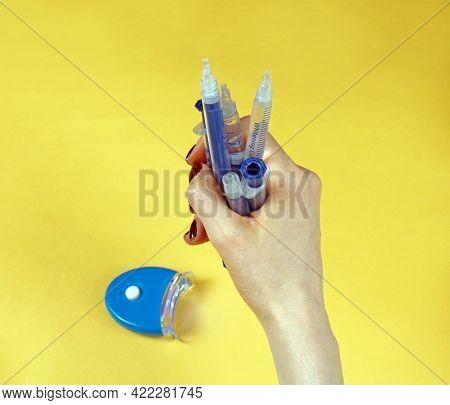 Female Hand Holding Plastic Syringes