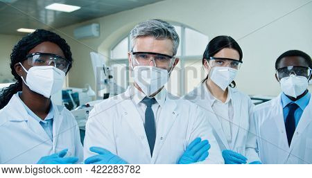Close Up Of Multi-ethnic Medical Experts In Masks And Goggles Standing In Hospital Lab Holding Test