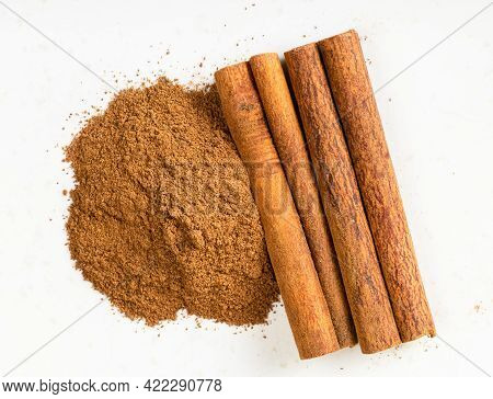 Top View Of Cinnamon Sticks And Powder Close Up On Gray Ceramic Plate