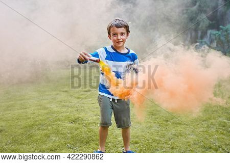Beautiful Boy Playing Outside With Colored Smoke Orange Color In Summer.