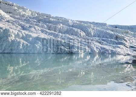 Natural Wall Formed By Travertine & Its Reflection In Pool, Pamukkale, Turkey. White Structure Seem