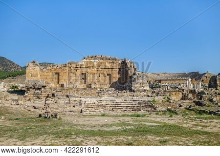 Ruins Of Apollo Temple In Ancient City Hierapolis, Pamukkale, Turkey. Remains Of Ploutonion On Right