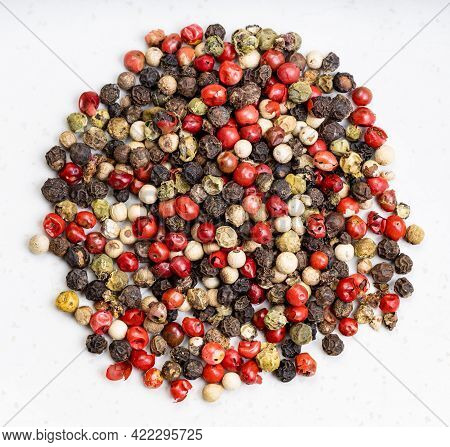 Top View Of Pile Of Four Pepper Blend Peppercorns Close Up On Gray Ceramic Plate