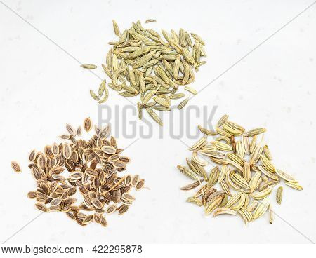 Three Pinches Of Anise, Dill And Fennel Seeds On Gray Ceramic Plate