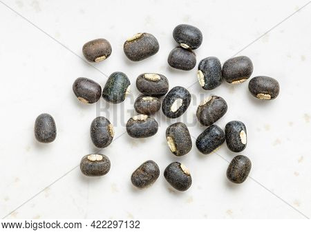 Several Raw Whole Black Urad Beans Close Up On Gray Ceramic Plate