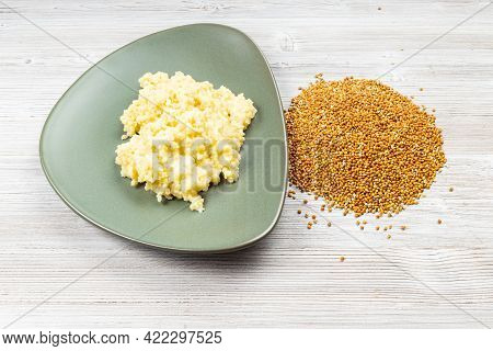 Whole Proso Millet Grains And Boiled Porridge On Green Plate On Wooden Table