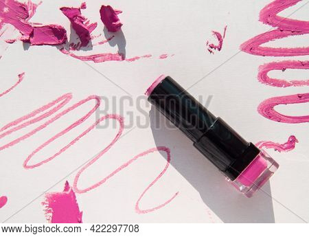 Black Used Tube Of Lipstick On A White Background, Various Smudged Lines And Textures Of Pink, Red L
