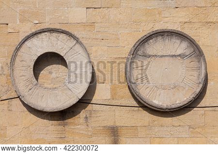 Watch Dials Attached To A Stone Wall.