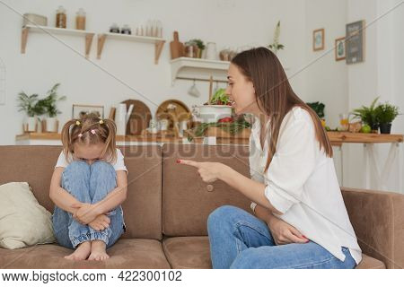 Single Mother And Little Child Are Sitting At Home On The Couch, Parent Scolds Preschool Daughter. T