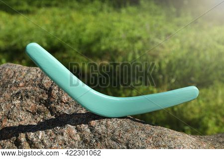Sunlit Turquoise Wooden Boomerang On Stone Outdoors
