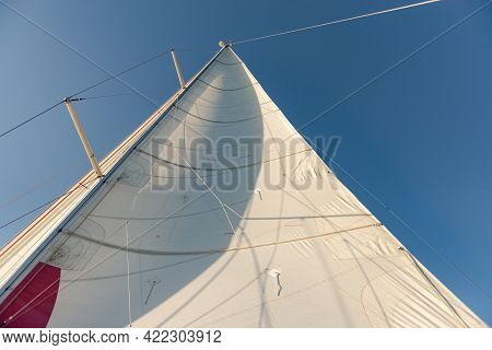 Sail Mainsail On A Yacht. Sail On A Yacht Filled With Wind. Photo From The Side Of The Yacht Up.
