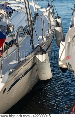 The Side Of A Yacht With Mooring Fenders Next To Another Yacht. Tight Mooring Of Yachts In The Marin