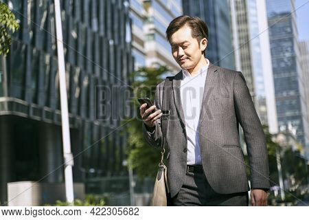 Asian White Collar Office Worker Looking At Mobile Phone While Walking To Work In Financial District