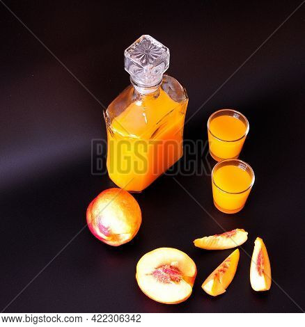 Two Ryums, A Decanter Of Homemade Apricot Liqueur And Ripe Fruit Pieces On A Black Background.