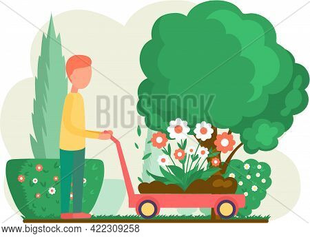 Male Worker Pushes Handcart With Flowers. Man Cultivating Plants On Backyard Flowers On Beautiful Fl