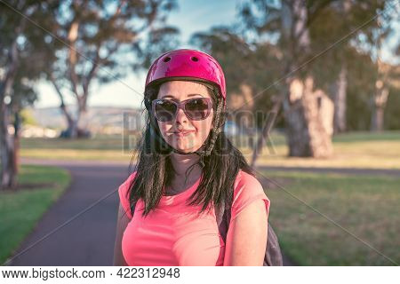 Natural Portrait Of Young Woman Wearing Sunglasses With Pink Top And Bike Helmet During Her Bike Rid