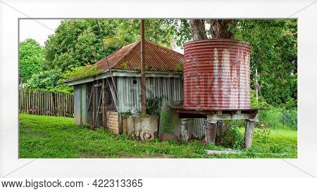 Old Shed And Water Tank In An Outdoor Backyard After Rainfall When The Grass And Foliage Are Lush An