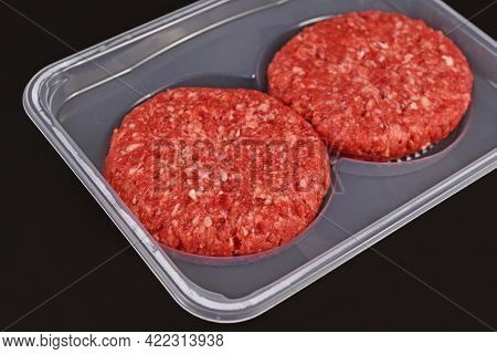 Round Raw Burger Patties In Package On Dark Background