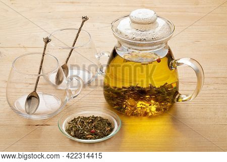 Glass teapot with a mixture of healthy herbal tea as a hot drink