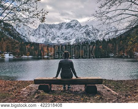 Woman Traveler Sits And Admires The Beautiful View Of The Snowcapped Mountains Against The Lake In I
