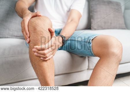 The Man Suffering From Knee Pain Sitting On The Couch Hold And Massaging His Painful Knee.