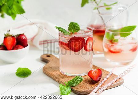 Homemade Refreshing Strawberry Lemonade In Glasses And Jug With Fresh Strawberries And Mint Leaves.