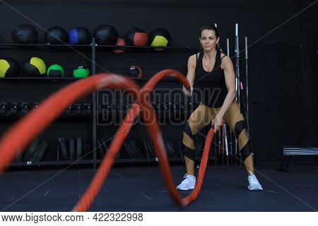 Fit Woman Using Battle Ropes During Strength Training At The Gym.