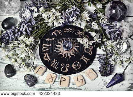 Still Life With Zodiac Circle, Runes, Crystal And Flowers On Witch Altar Table.  Esoteric, Gothic An