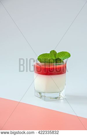 Panna Cotta With Strawberry Sauce In A Glass Glass.