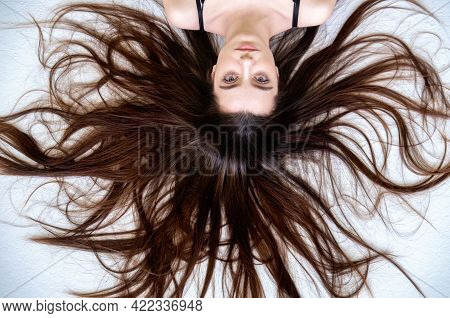 Beautiful Young Sexy Woman Lying On The White Background With Long Widespread Sprawled Brown Hair