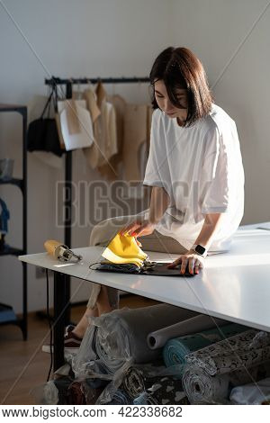 Fashion Designer Or Tailor Woman Choose Swatches Of Fabric In Design Studio. Female Sewer Look At Sa