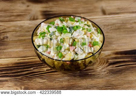 Salad With Crab Sticks, Sweet Corn, Cucumber, Eggs, Rice And Mayonnaise On Wooden Table