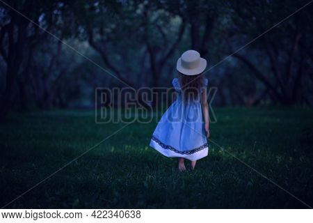 View From The Back Of A Girl In A Blue Dress Runs Barefoot In The Park. Fabulous Mysterious Forest
