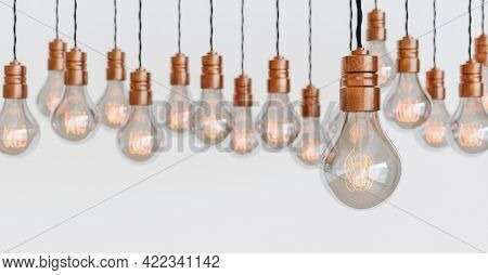 Many Vintage Light Bulbs Hanging With Copper Bulb Holders And Orange Filament. Blurred Background. W