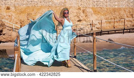 A Beautiful Slender Woman With Curly Hair In A Fluttering Blue Long Evening Luxurious Dress Near The