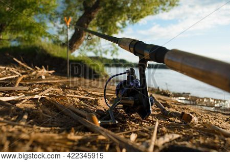 Fishing Rod On The Shore Of The Lake. Close-up Of A Spinning Reel, Selective Focus. Fishing Concept.