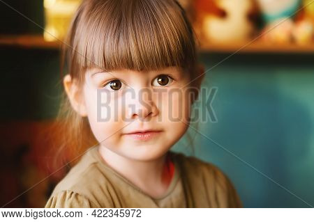 Funny Little Girl Looks At The Camera Sitting At Home. Cute, Pretty, Small Girl With Beautiful Big B