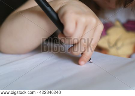 A Child's Hand Holds A Large Black Ballpoint Pen And Draws On A White Piece Of Paper. Selective Focu