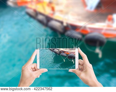 Tourist Hand Holding Mobile Photograph Picture Blue Sea And Boat. For Nature Tropical Summer Travel