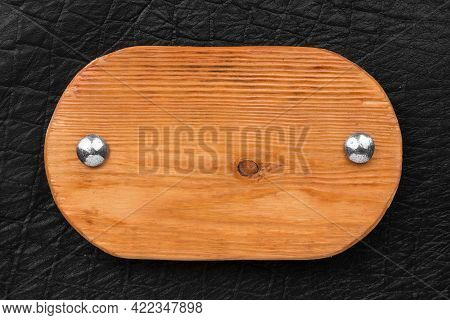 Sign Made From A Board, Fastened With Iron Rivets On Black Leather. Top View. Old Wooden Signboard