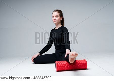 Beautiful Girl Trainer Doing Stretching Using The Fascia Stretching Her Leg In The Gym. Isolated On