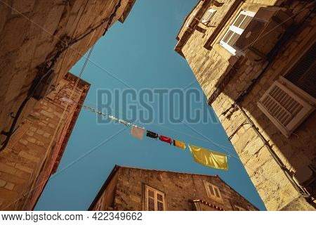 Croatia. Sunny Day in Dubrovnik. The Clothes Drying out on the Rope. Typical Balkan Street. Perspective View on Old Historical Buildings.