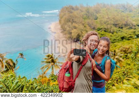 Hikers couple taking selfie on Hawaii travel hiking on Kalalau trail overlooking Na Pali beach. Two tourists with backpacks walking outdoor in Hanalei Bay, Kauai island, summer active lifestyle.