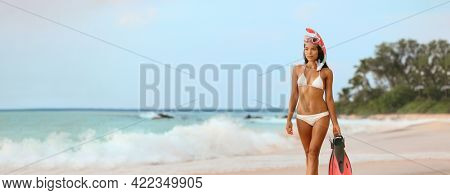 Beach vacation elegant Asian lady going swimming in ocean with snorkel equipment at Caribbean tropical destination. Swimsuit bikini model luxury lifestyle banner panoramic.