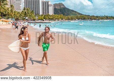 Hawaii surf lifestyle couple of surfers going surfing in Waikiki beach, Honolulu, Oahu island. USA travel. Fun summer tourist vacation destination activity.