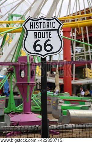 May 14, 2021 Santa Monica California, USA:  Historic Route 66 sign. Route 66 Sign on the Santa Monica Pier with carnival rides in the background. Editorial Use Only.