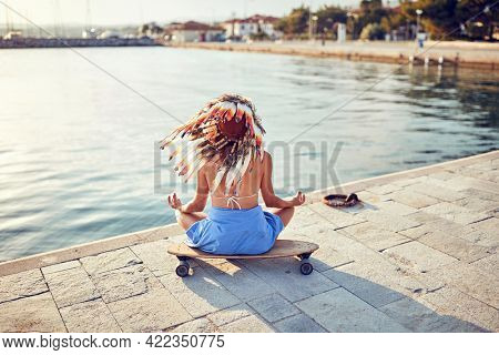 A young sexy girl with an indian war bonnet on her head is sitting on a skateboard in the dock at sea and meditating on a beautiful sunny day. Summer, sea, vacation