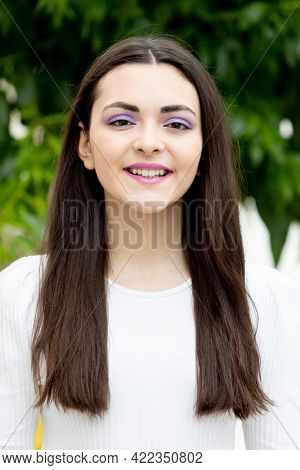 Cute young woman with  purple eyeshadow outside