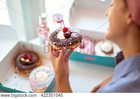 A beautiful girl in a pleasant atmosphere in a pastry shop is amazed by delicious donut she holds in her hand. Pastry shop, dessert, sweet