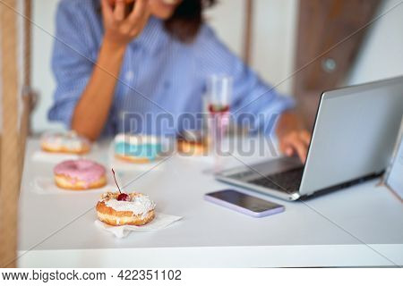 A woman is eating delicious donuts while sitting and using a laptop in a pleasant atmosphere in a pastry shop. Pastry shop, dessert, sweet